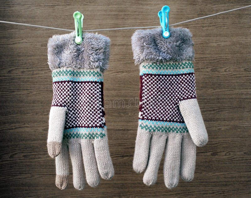 Earth tone winter gloves with green and blue clothes pin hanging on white clothes line rope with dark brown wooden background. Close-up earth tone winter gloves stock photos