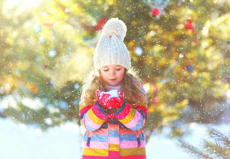 Winter happy little child holds blowing snow on hands royalty free stock photos