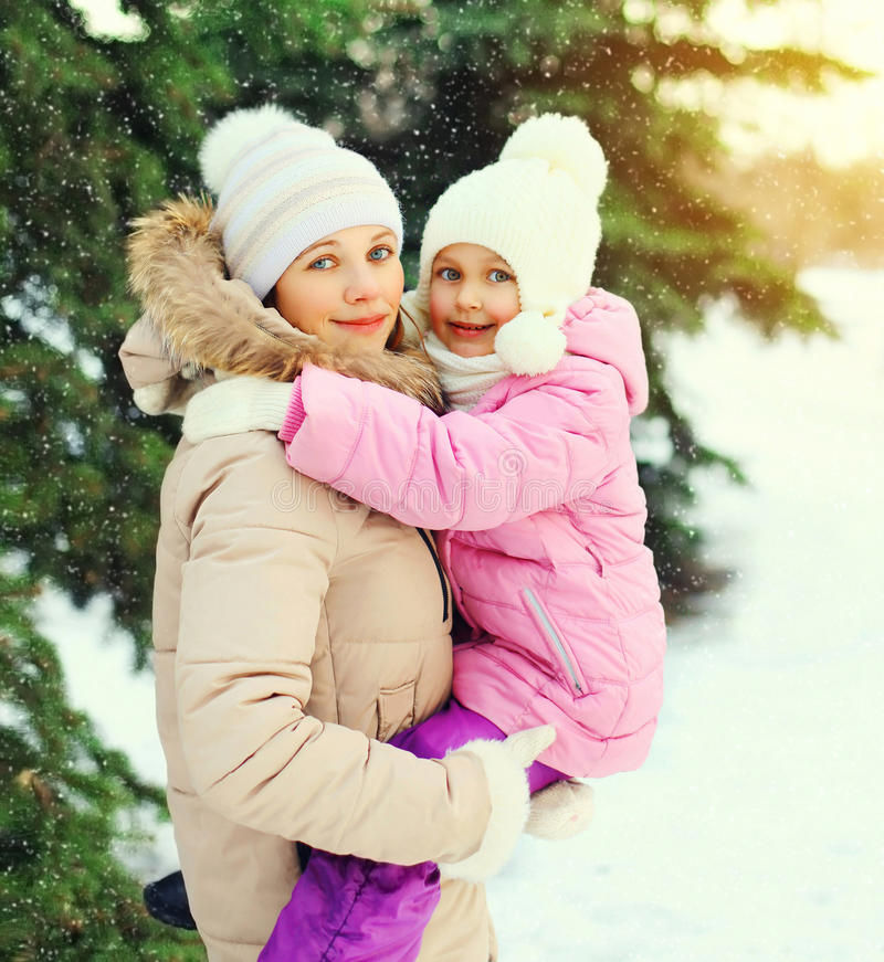 Winter happy mother and child over christmas tree snowflakes stock photo