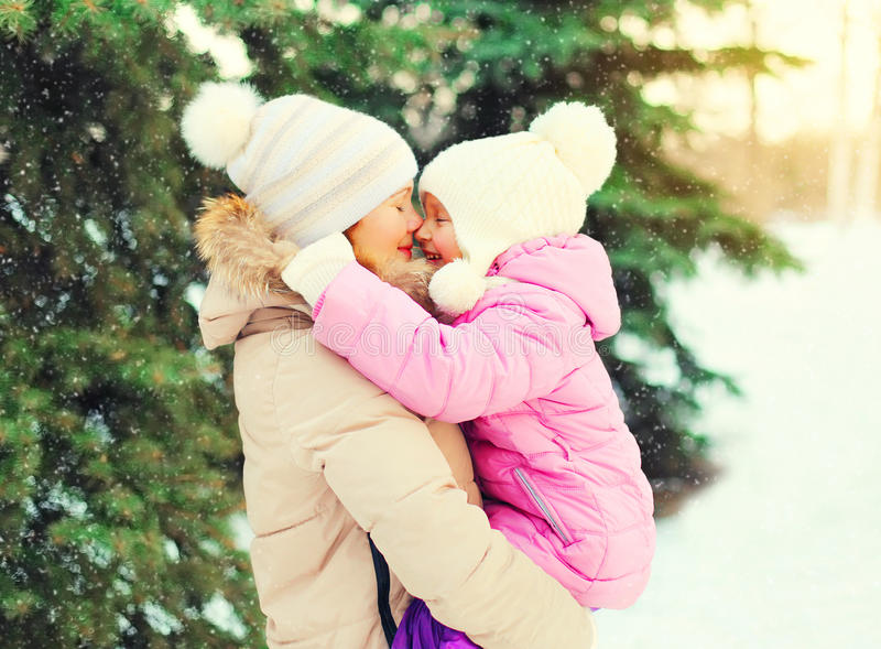 Winter happy mother hugging child over christmas tree snowflakes royalty free stock photos