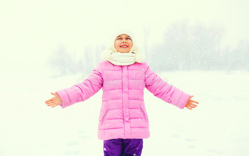 Winter happy smiling little girl child enjoys snowflakes in snow royalty free stock image