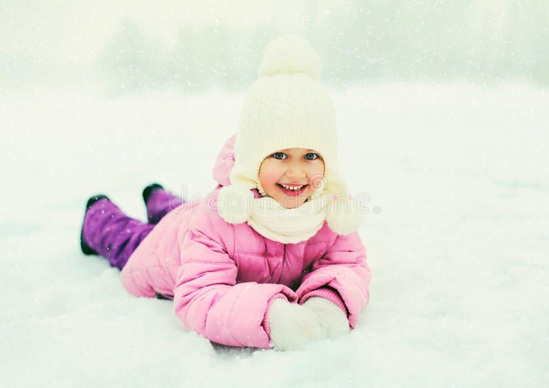 Winter happy smiling little girl child playing on snow royalty free stock photos