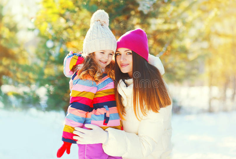Winter happy smiling mother and child over snowy sunny royalty free stock image