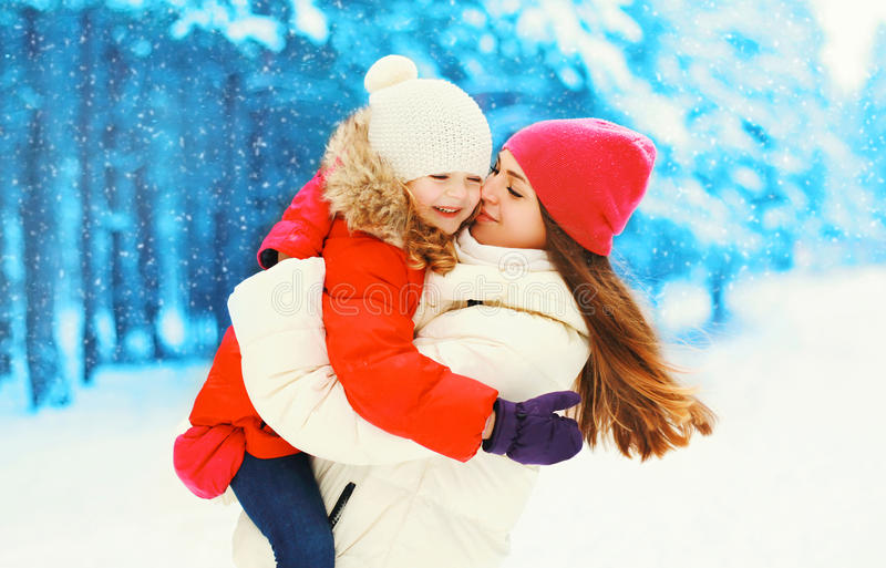 Winter happy smiling mother hugging kissing child over snowflakes royalty free stock photography