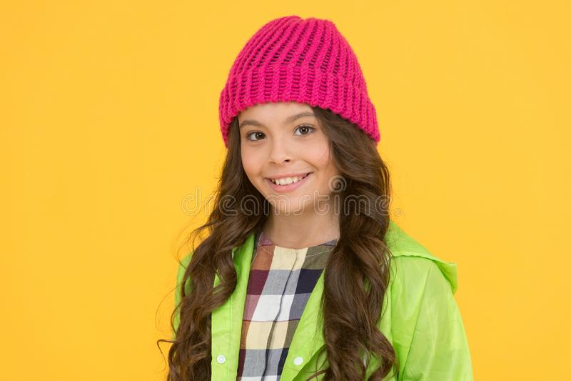 Winter hat styles. Kid girl wear knitted hat. Winter accessory concept. Girl long hair yellow background. Cold season. Concept. Winter fashion accessory. Small royalty free stock photography