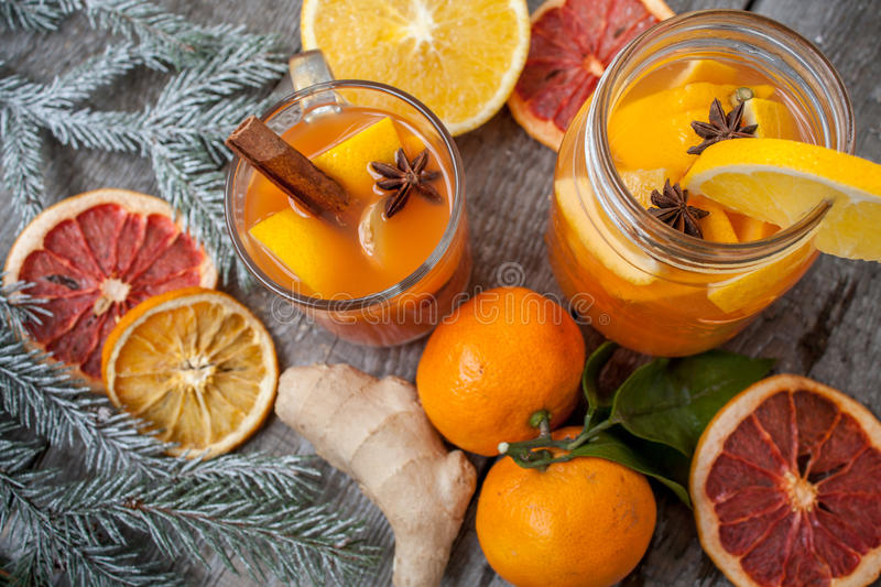 Winter healing ginger drink with lemon, honey and oranges. Cinnamon, star anise, fir twigs, tangerines, dried grapefruit. Winter christmas background, top view royalty free stock photo