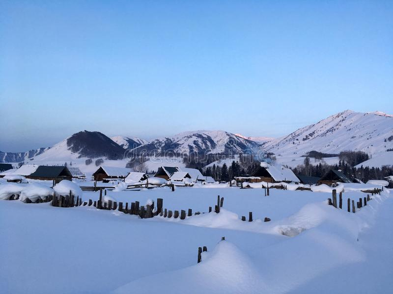 Winter Hemu village in Xinjiang, China. Heavy snow-covered wooden houses in Hemu village in winter. Located within the Kanas Lake scenic area in the north of stock photo