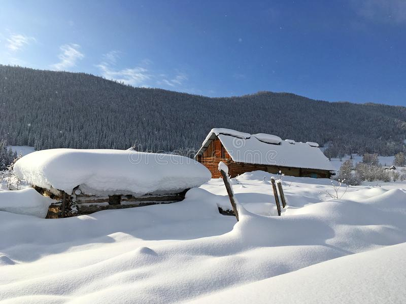 Winter Hemu village in Xinjiang, China. Heavy snow-covered wooden houses in Hemu village in winter. Located within the Kanas Lake scenic area in the north of royalty free stock image