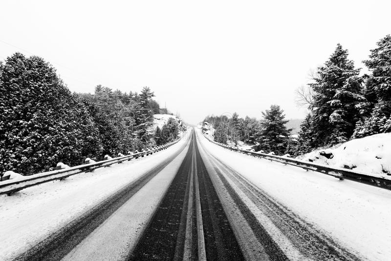 Highway in winter with guardrails. Winter scene with snow covered trees, ice and snow on a highway in Ontario, Canada royalty free stock photos
