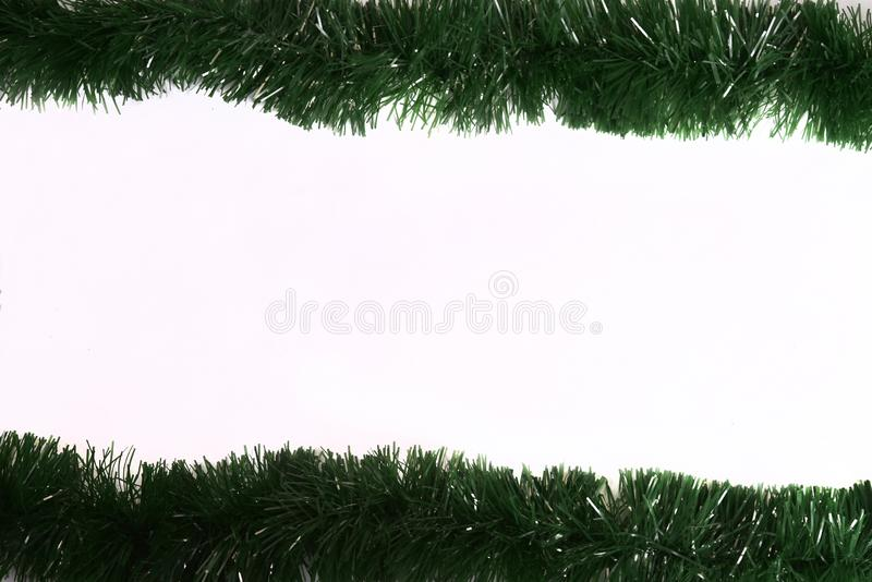 Winter holiday background. Border with Christmas tree branches and ornaments isolated on blue. Fir needles garland, frame with stock photo