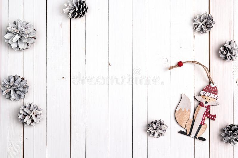 Winter holiday background with fox and snow painted pine cones o. N white wooden table. Space for text. Top view royalty free stock photography