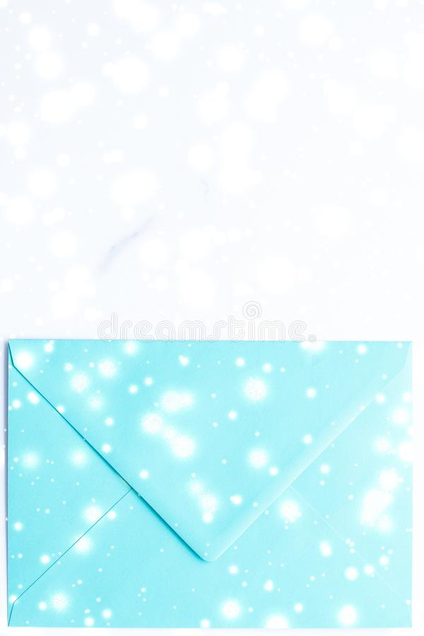 Winter holiday blank paper envelopes on marble with shiny snow flatlay background, love letter or Christmas mail card design. Greetings, postal service and stock photos