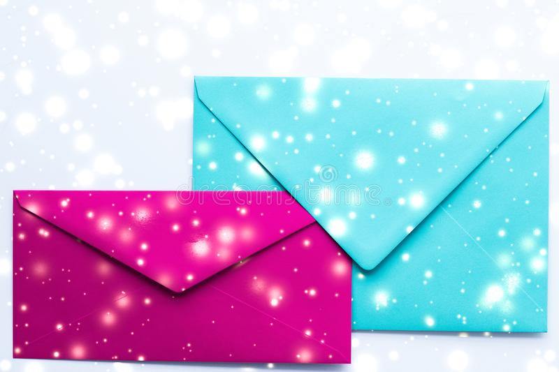 Winter holiday blank paper envelopes on marble with shiny snow flatlay background, love letter or Christmas mail card design. Greetings, postal service and royalty free stock image