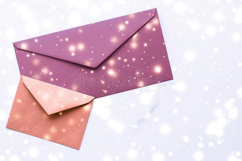 Winter holiday blank paper envelopes on marble with shiny snow flatlay background, love letter or Christmas mail card design royalty free stock photos