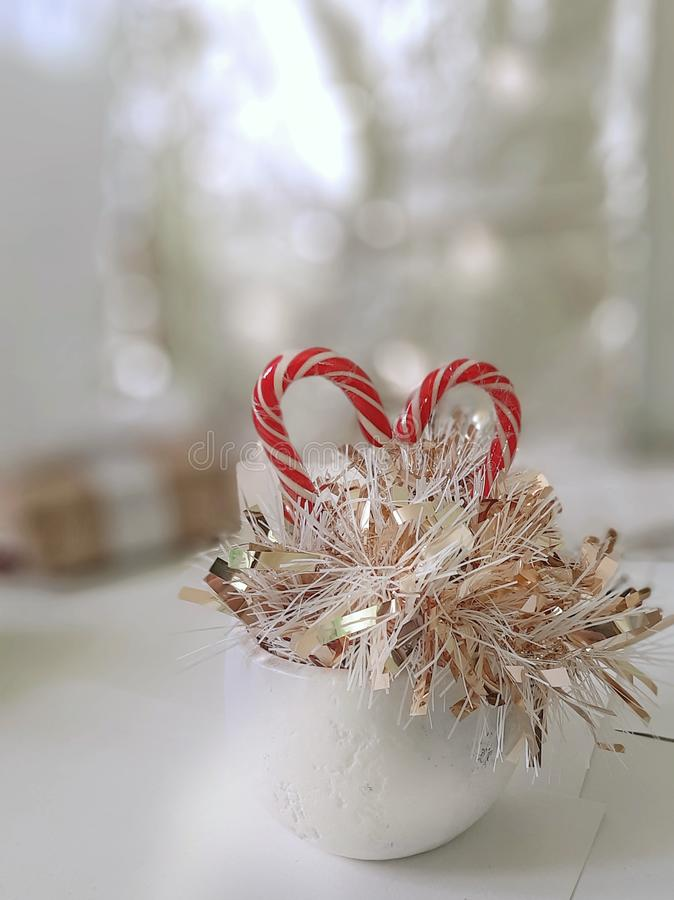 Winter holiday composition. Sweet candy heart, golden tinsel in white ceramic pot on bright background royalty free stock photography