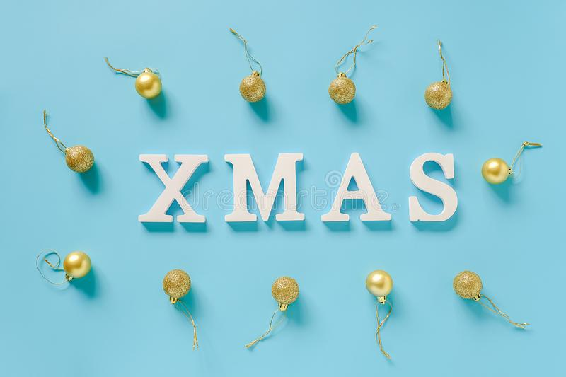 Winter holiday composition. Text Xmas from white letters and christmas decoration golden balls on blue background stock photos