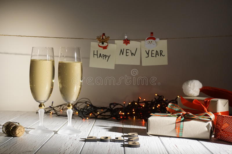 Winter holiday concept consisting of two glasses of champagne, wrapped presents, garlands and happy new year sign royalty free stock photography