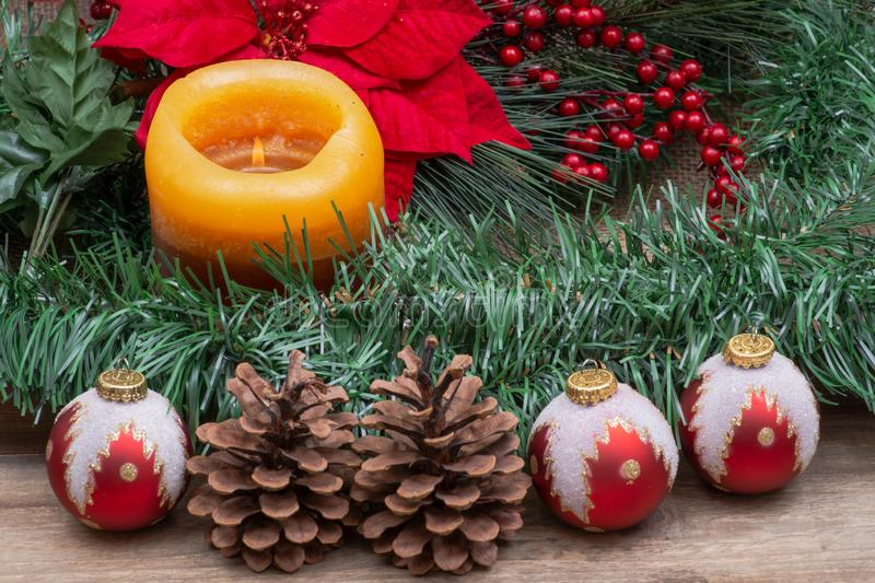 Winter holiday decoration: Blooming Red Poinsettia, Pine, Berry bush, Christmas tree balls, pine cone, walnuts and burning candle. On wooden background stock photos