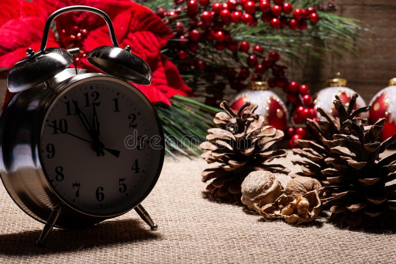Winter holiday decoration, Christmas and New Year concept with alarm clock:Red Poinsettia, Pine, Berry bush. Winter holiday decoration, Christmas and New Year stock photos