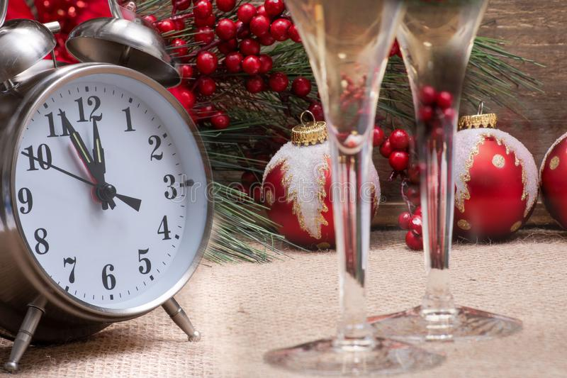 Winter holiday decoration, Christmas and New Year concept with alarm clock: Blooming Red Poinsettia, Pine, Berry bush, Christmas. Tree balls, glasses of wine on stock photo