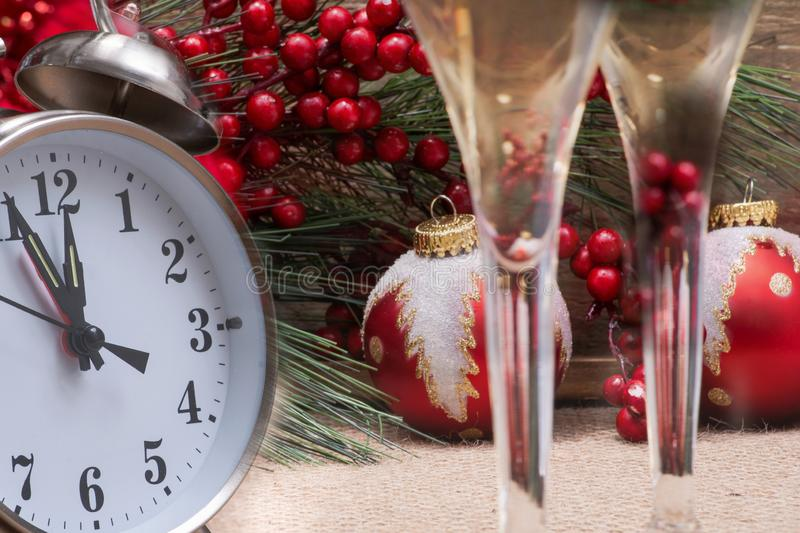 Winter holiday decoration, Christmas and New Year concept with alarm clock: Blooming Red Poinsettia, Pine, Berry bush, Christmas. Tree balls, glasses of wine on royalty free stock image