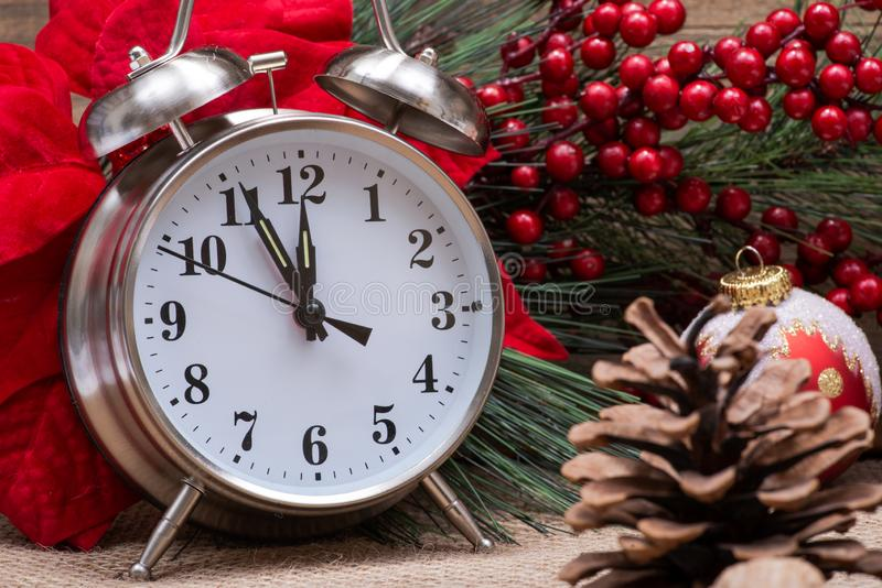 Winter holiday decoration, Christmas and New Year concept with alarm clock:Red Poinsettia, Pine, Berry bush. Winter holiday decoration, Christmas and New Year royalty free stock photos