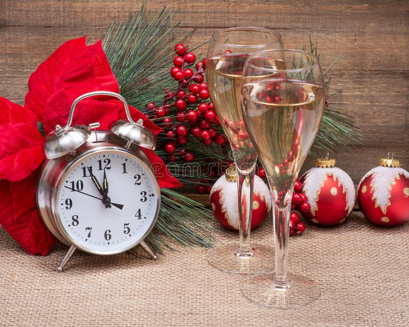 Winter holiday decoration, Christmas and New Year concept with alarm clock:Red Poinsettia, Pine, Berry bush. Winter holiday decoration, Christmas and New Year royalty free stock images