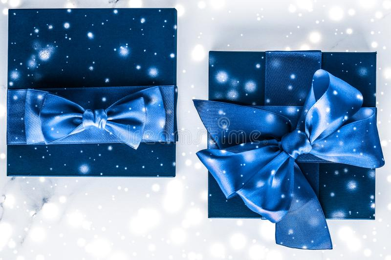 Winter holiday gift box with blue silk bow, snow glitter on marble background as Christmas and New Years presents for luxury. Branding, glamour and cold season royalty free stock image