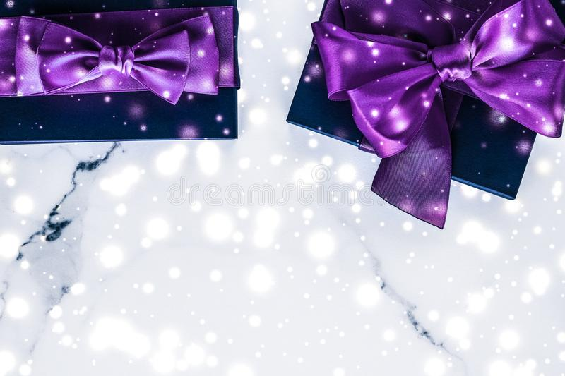Winter holiday gift box with purple silk bow, snow glitter on marble background as Christmas and New Years presents for luxury. Branding, glamour and cold season royalty free stock photos
