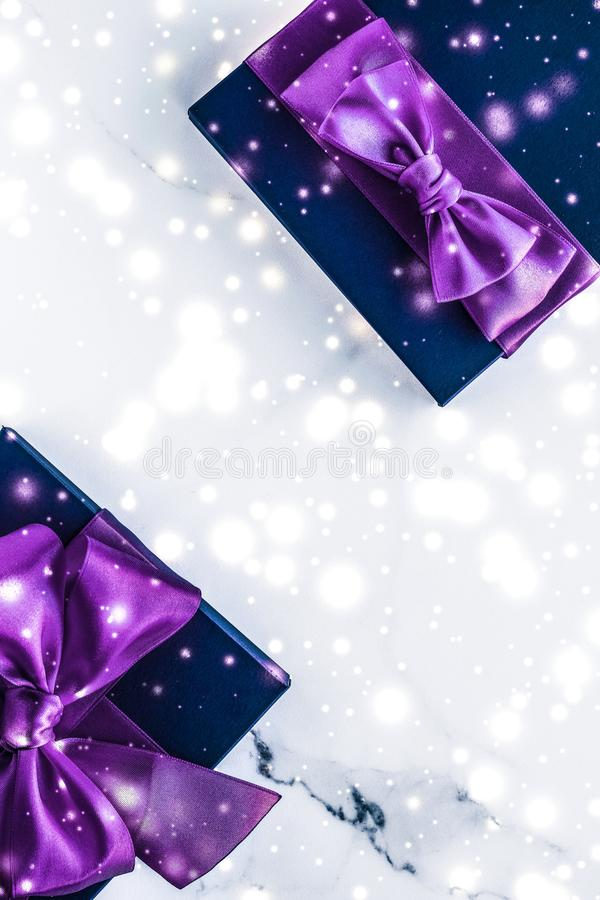 Winter holiday gift box with purple silk bow, snow glitter on marble background as Christmas and New Years presents for luxury. Branding, glamour and cold season stock photo