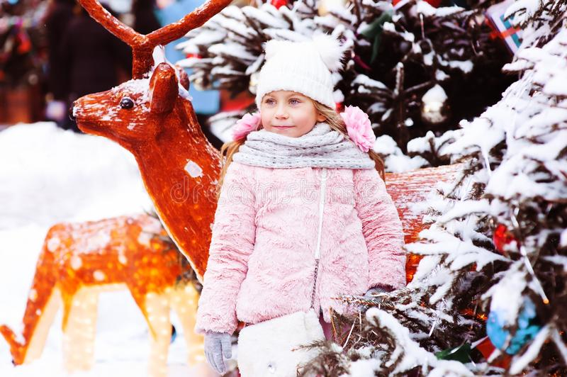 winter holiday portrait of happy child girl walking in city decorated for Christmas and New Year stock photography
