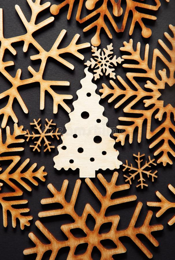 Winter holidays background with handmade wooden elements. Beautiful handmade wooden Christmas Tree toy in flat lay on black background.Vertical postcard image stock photo