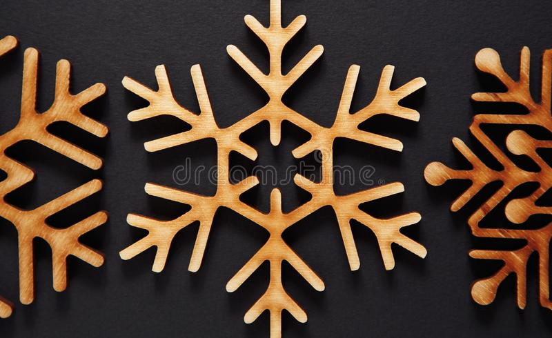 Winter holidays background with handmade wooden elements. Decortive wooden snowflake in flat lay on black background for Christmas party wallpaper design stock images