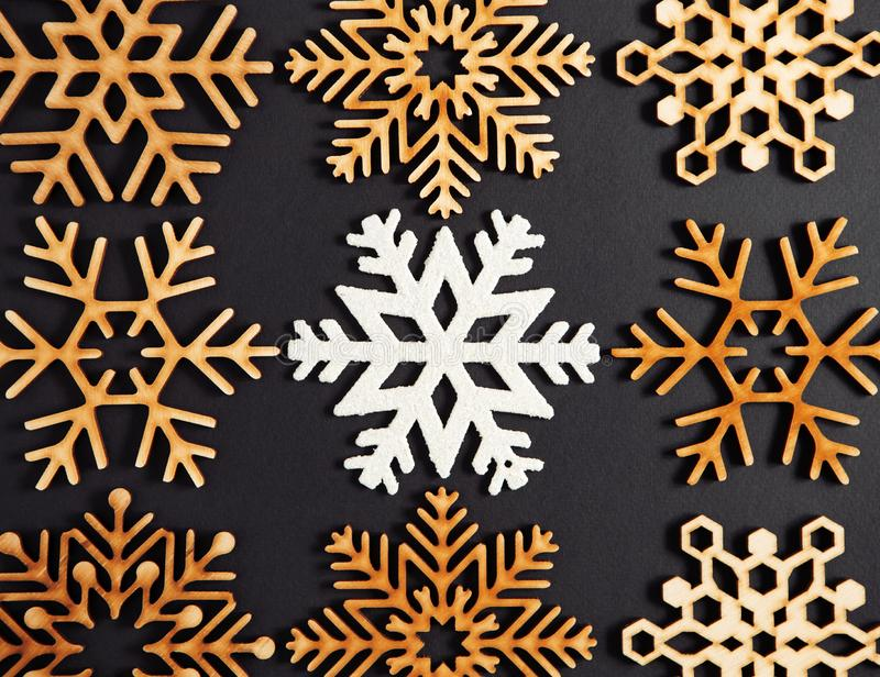 Winter holidays background with handmade wooden elements. Flat lay black Christmas background.Wooden decorative snowflakes shot directly from above.New Year royalty free stock photo