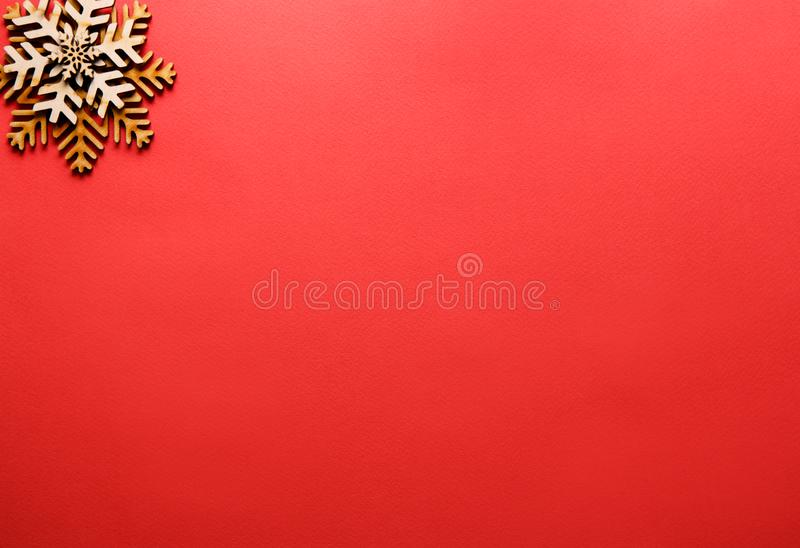 Winter holidays background with handmade wooden elements. Flat lay red Christmas background with handmade wooden snowflakes in corner.Empty space for text on stock photography