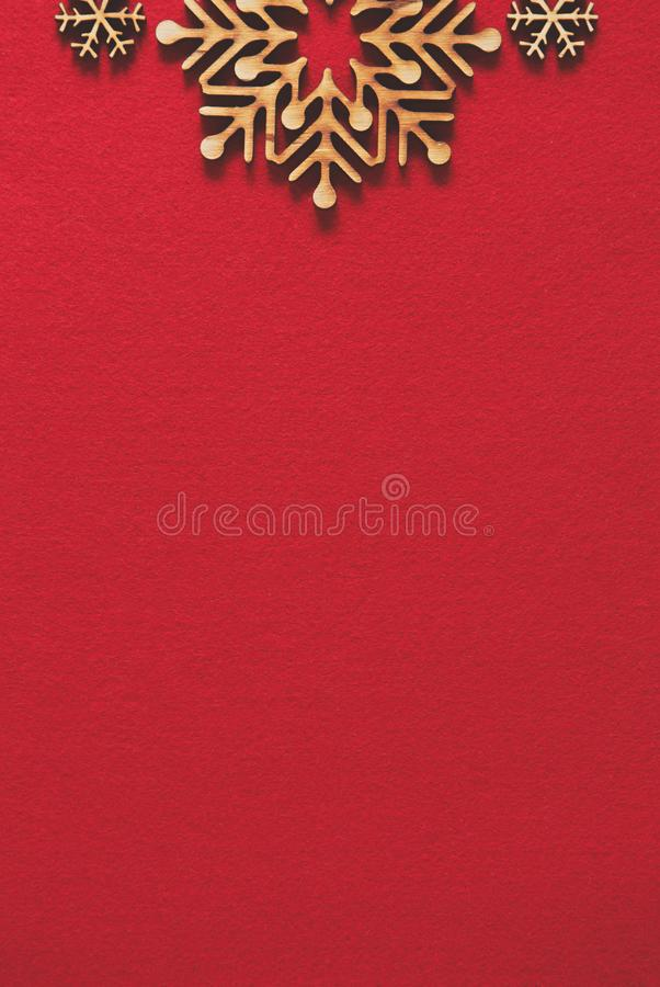 Winter holidays background with handmade wooden elements. Flat lay red Christmas background with wooden snowflakes.Vertical New Year poster template with empty royalty free stock image