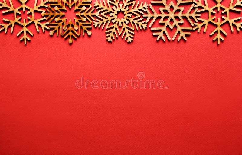 Winter holidays background with handmade wooden elements. Red Christmas background.Flat lay wooden snowflakes shot directly from above.New Year party poster royalty free stock images