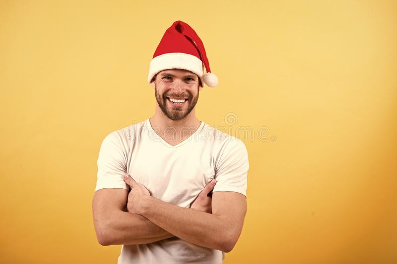 Winter holidays celebration concept. Man santa smile with folded hands on orange background. Macho in red xmas hat and white tshirt. Christmas and new year stock photography