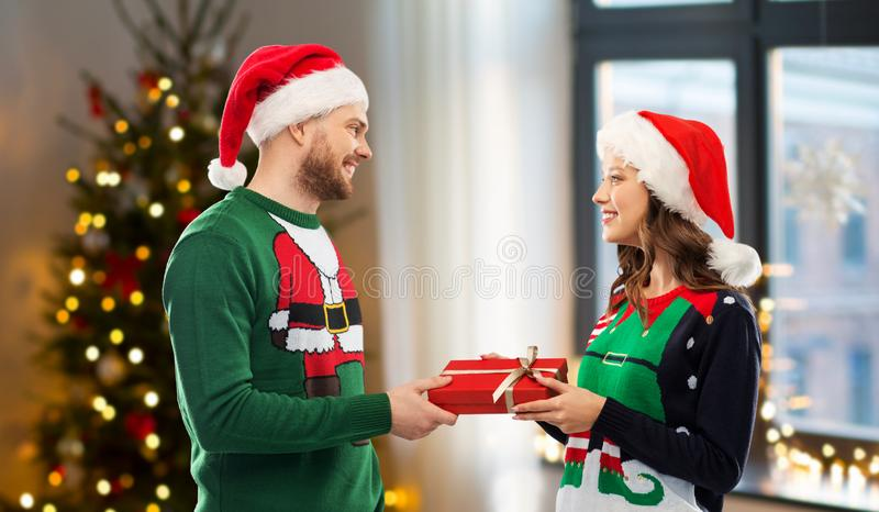 Happy couple in sweaters with christmas gift royalty free stock images