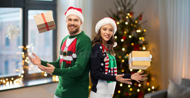 Happy couple in sweaters with christmas gifts royalty free stock photo