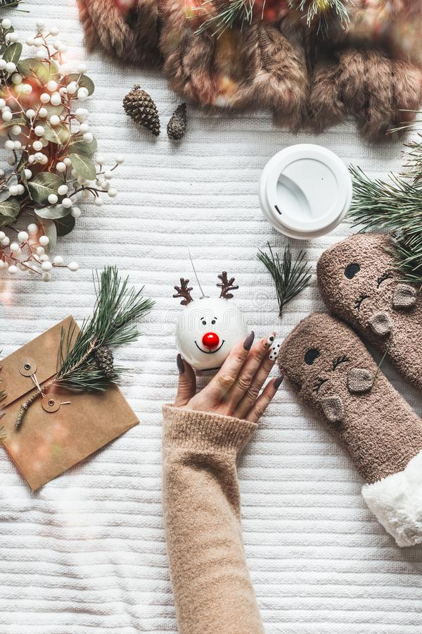 Winter holidays and Christmas concept. Female hand holding funny snowman toy on white blanket with pine branches, fur wrap, stock images