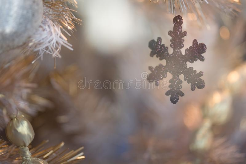 Winter Holiday silver white tinsel Christmas tree with snowflake ornament and lights royalty free stock photography
