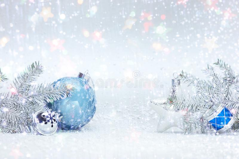 Winter holidays composition on white snow with christmas tree branches, decorative blue ball, silver glass star and drums toy stock photos