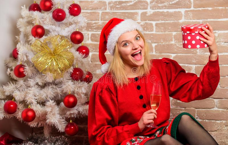 Winter holidays concept. Girl wear red dress sit near christmas tree. Woman hold glass champagne and gift box. Girl. Relax near christmas tree. Unpacking royalty free stock photos