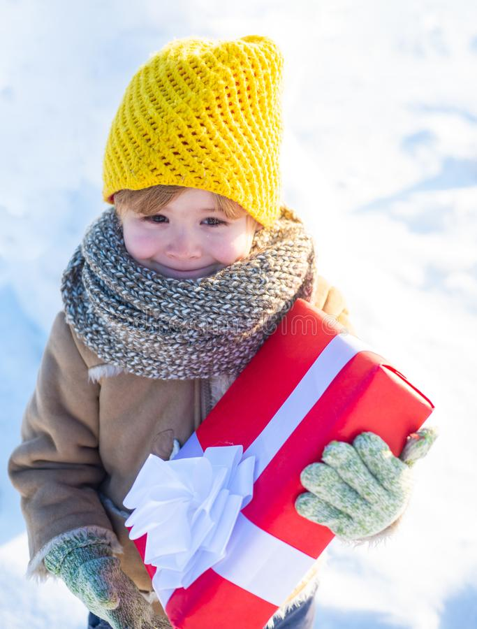 Winter holidays concept. May you have wonderful holiday. Happy winter child hold gift bow snow background. Cute boy in stock photo