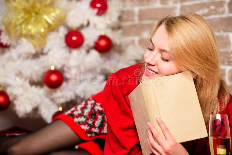 Winter holidays concept. Waiting for christmas. Girl wear red dress sit near christmas tree. Woman hold glass champagne. And book. Lady celebrate christmas royalty free stock image