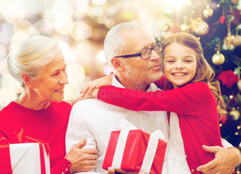 Happy family with christmas gifts over lights royalty free stock photo