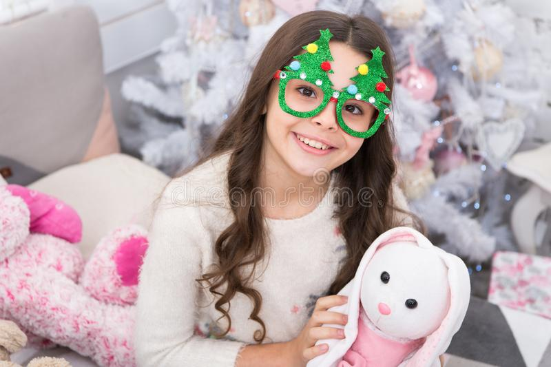 Winter holidays. Kid relaxing. Adorable little girl wear christmas tree glasses photo booth props. Rest and relax. Christmas eve. Small girl at home christmas royalty free stock images