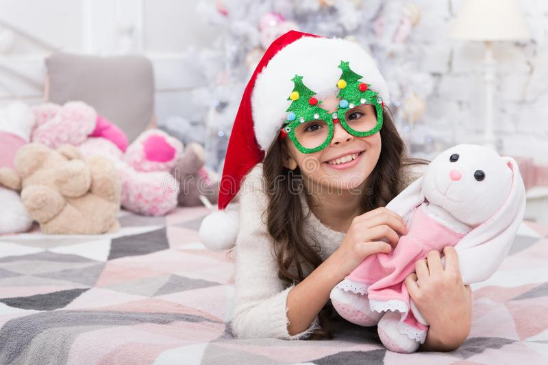 Winter holidays. Kid relaxing in bedroom. Adorable little girl wear christmas tree glasses photo booth props. Christmas. Eve. Small girl at home christmas royalty free stock images