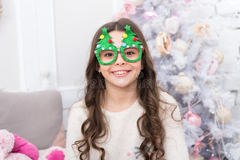 Winter holidays. Kid relaxing in bedroom. Adorable little girl wear christmas tree glasses photo booth props. Rest and. Relax. Christmas eve. Small girl at home royalty free stock photos